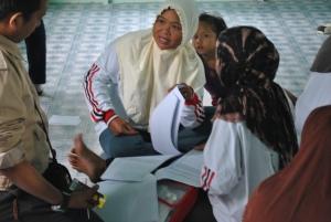 Salah satu Relawan Desa bertanya kepada fasilitator bagaimana cara mengisi pelaporan yang benar.