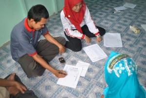 Fasilitator dan relawan Desa sedang melakukan pelaporan
