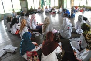 relawan kelurahan memperhatikan materi tentang malaria dari fasilitator