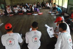 relawan kelurahan mendengarkan penjelasan tentang malaria dari fasilitator