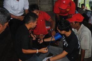 relawan kelurahan mencoba belajar menggunakan alat pengukur tekanan darah