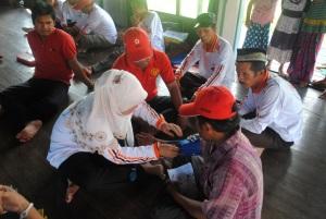 relawan kelurahan belajar mencoba menggunakan alat pengukur tekanan darah