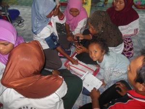 Relawan Desa sedang mencoba belajar menggunakan alat pengukur tekanan darah