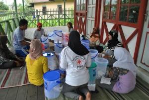 relawan kelurahan mencoba memasang keramik filter