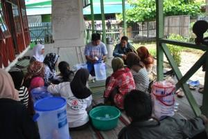 fasilitator menjelaskan kepada relawan kelurahan bagaimana memasang keramik filter yang benar